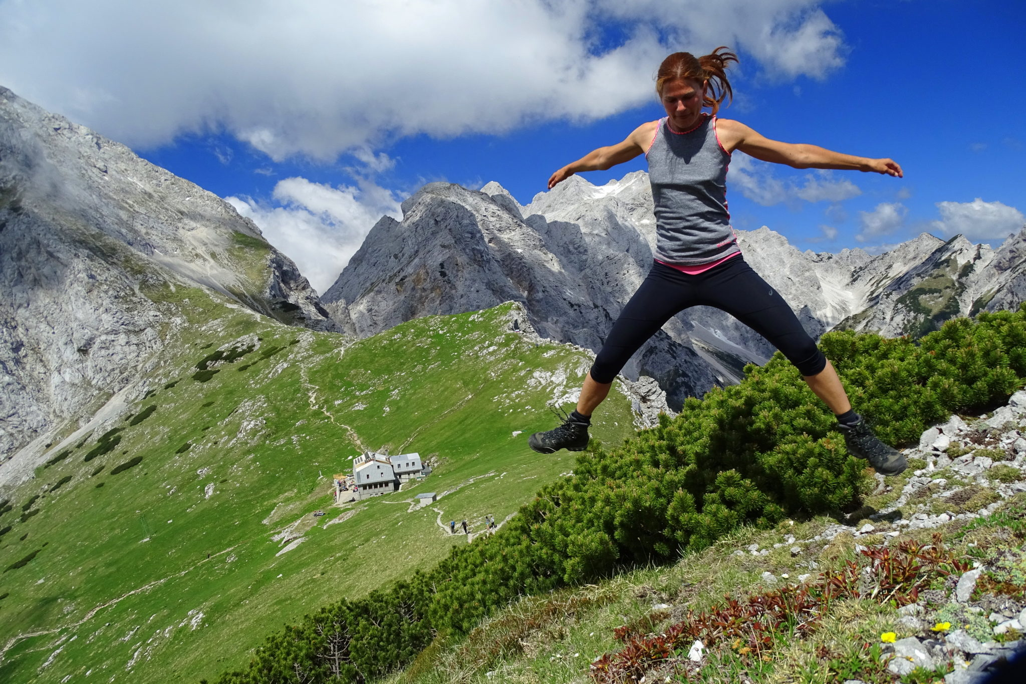 A woman hiker jumping with joy on an Alpine meadow
