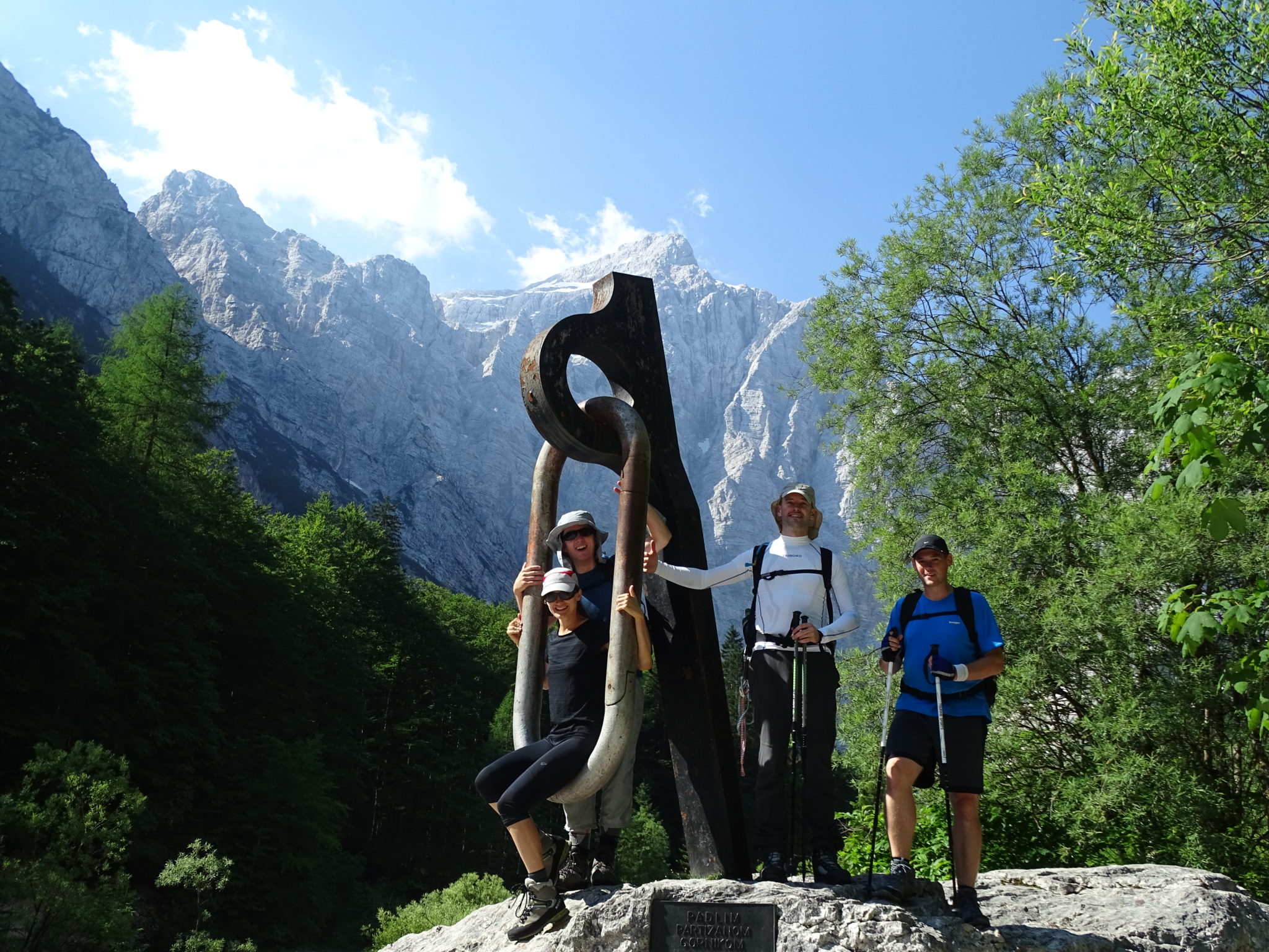 A group of hikers in the Vrata Valley and behind the Triglav North Face