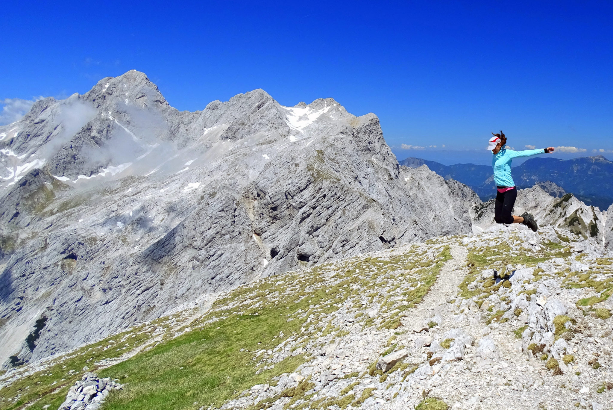 A woman hiker jumping with joy to have climbed a high mountain in Slovenia