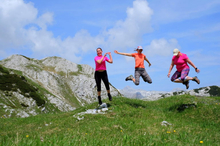 Three women hikers jumping in the mountains, Slovenia, Triglav National Park